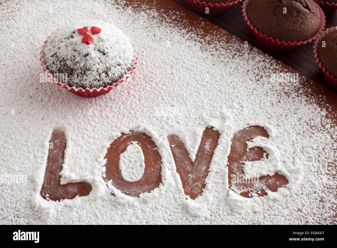 High Angle View Of Text In Powdered Sugar By Muffin On Cutting Board - Stock Image