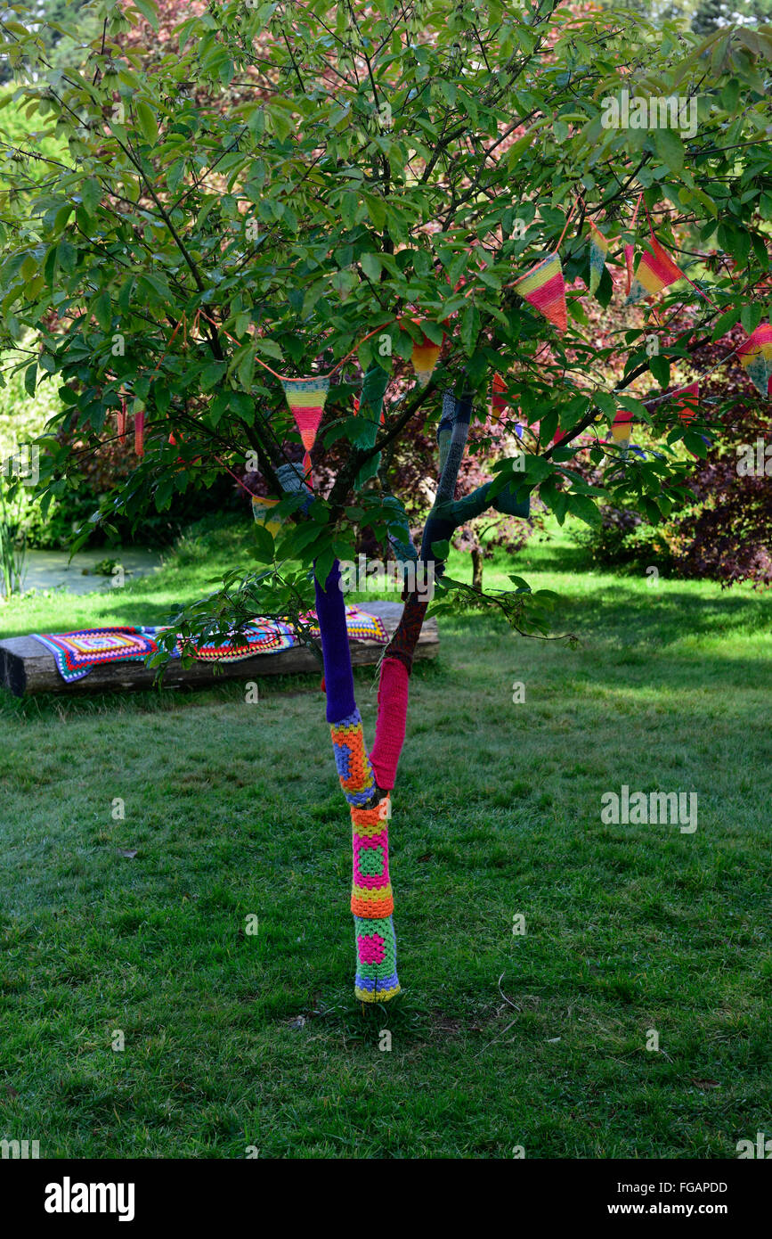 Tree trunk cover covered wool woolen knit knitting knitted cover art artistic installation garden RM Floral - Stock Image