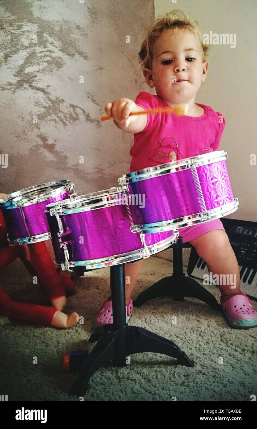 Cute Girl Playing Drum At Home - Stock Image