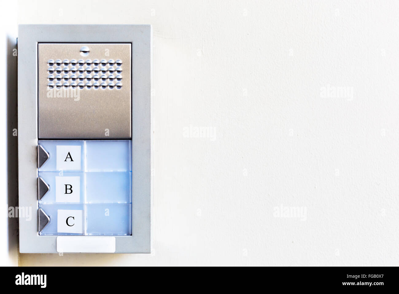 Silver door buzzer with 3 buttons labelled ABC on left, empty white wall on right of image. - Stock Image