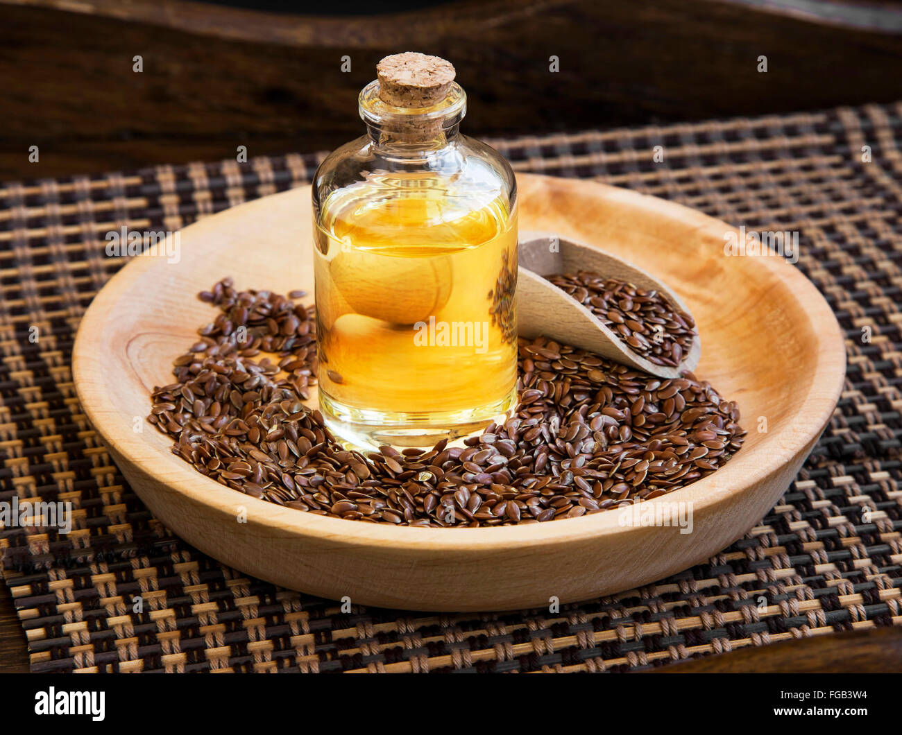 Flax seed oil in transparent bottle with flax seeds - Stock Image