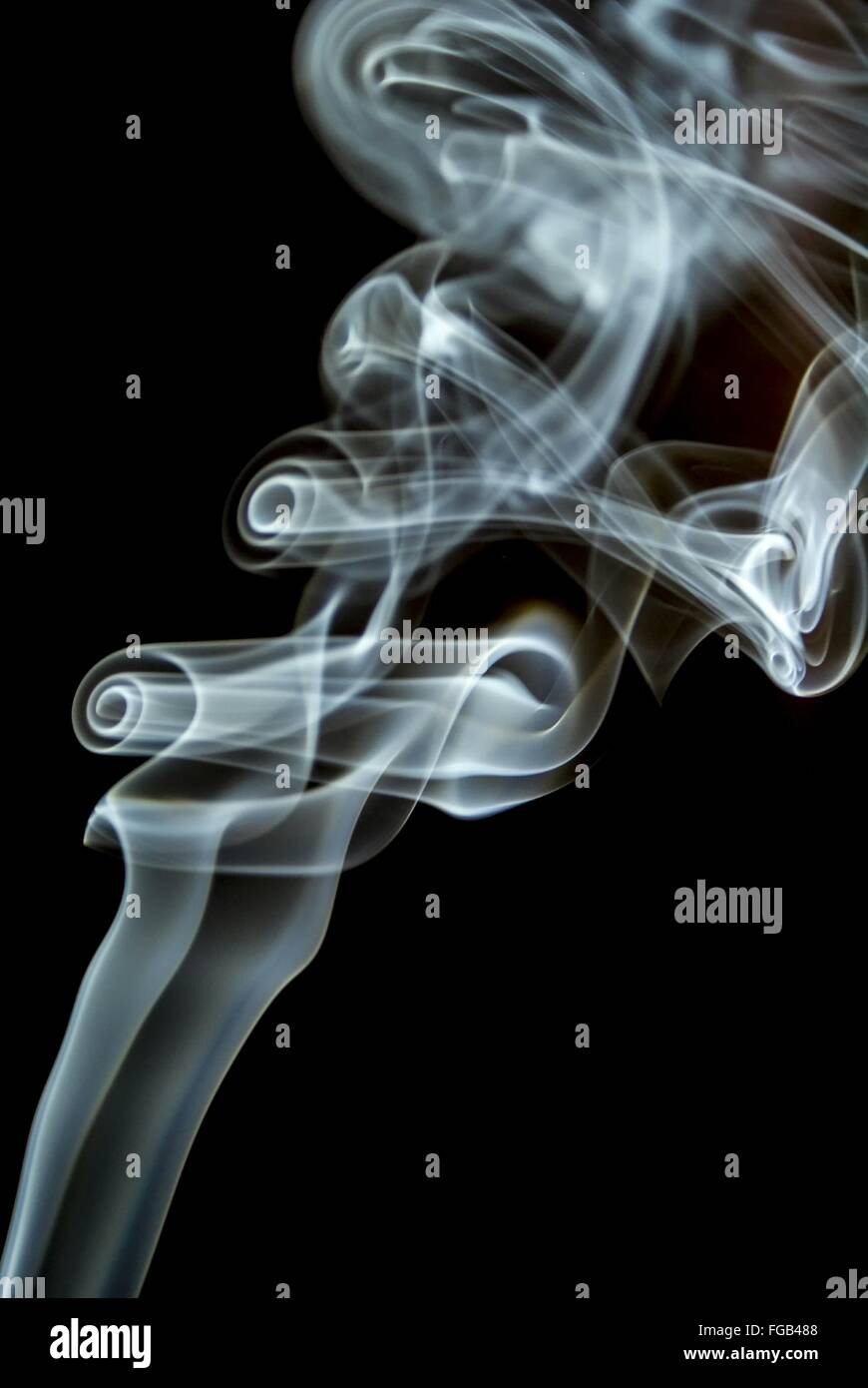 Close-Up Of Incense Smoke Against Black Background - Stock Image