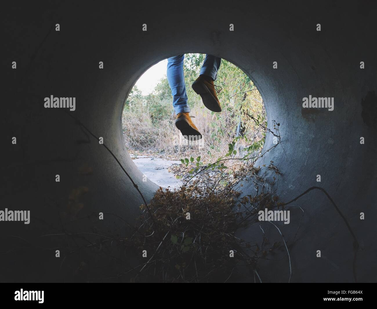 Low Section Of Man Legs Seen Through Pipe - Stock Image