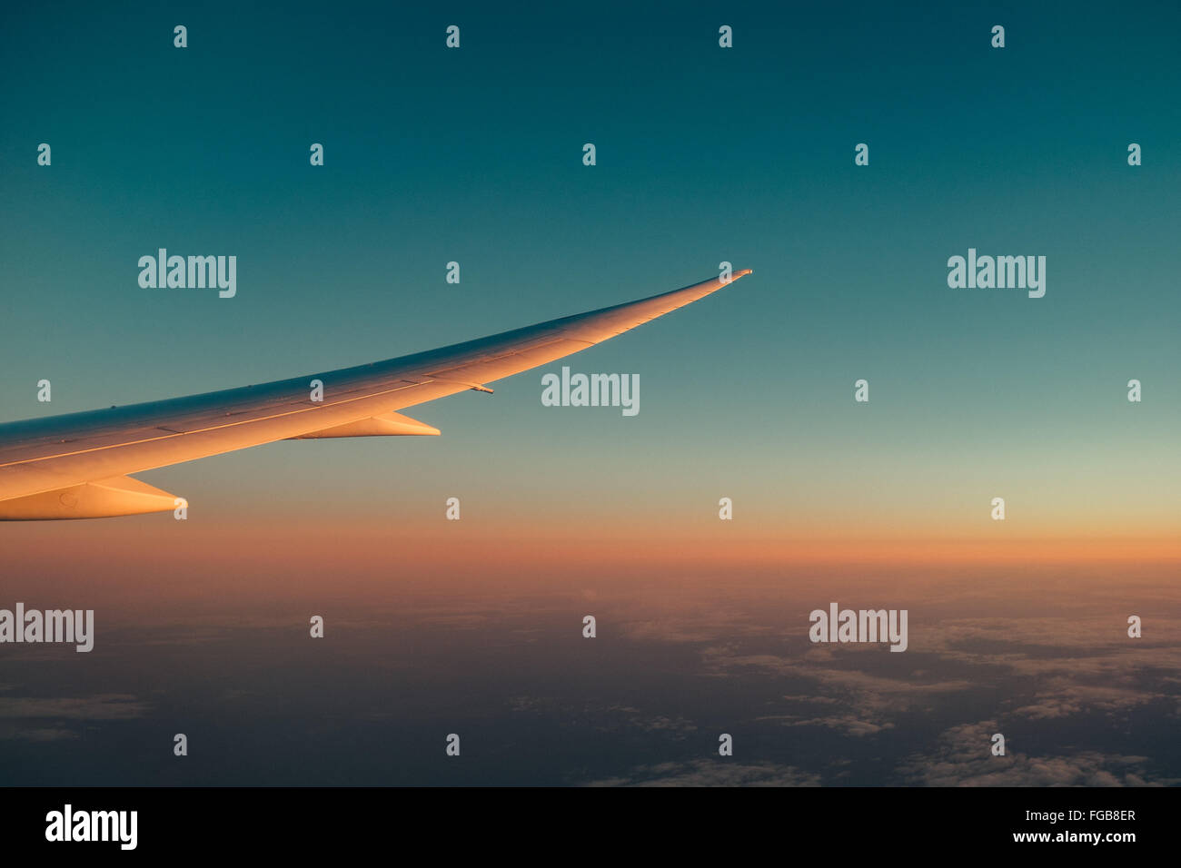 Cropped Airplane Wing Against Blue Sky - Stock Image