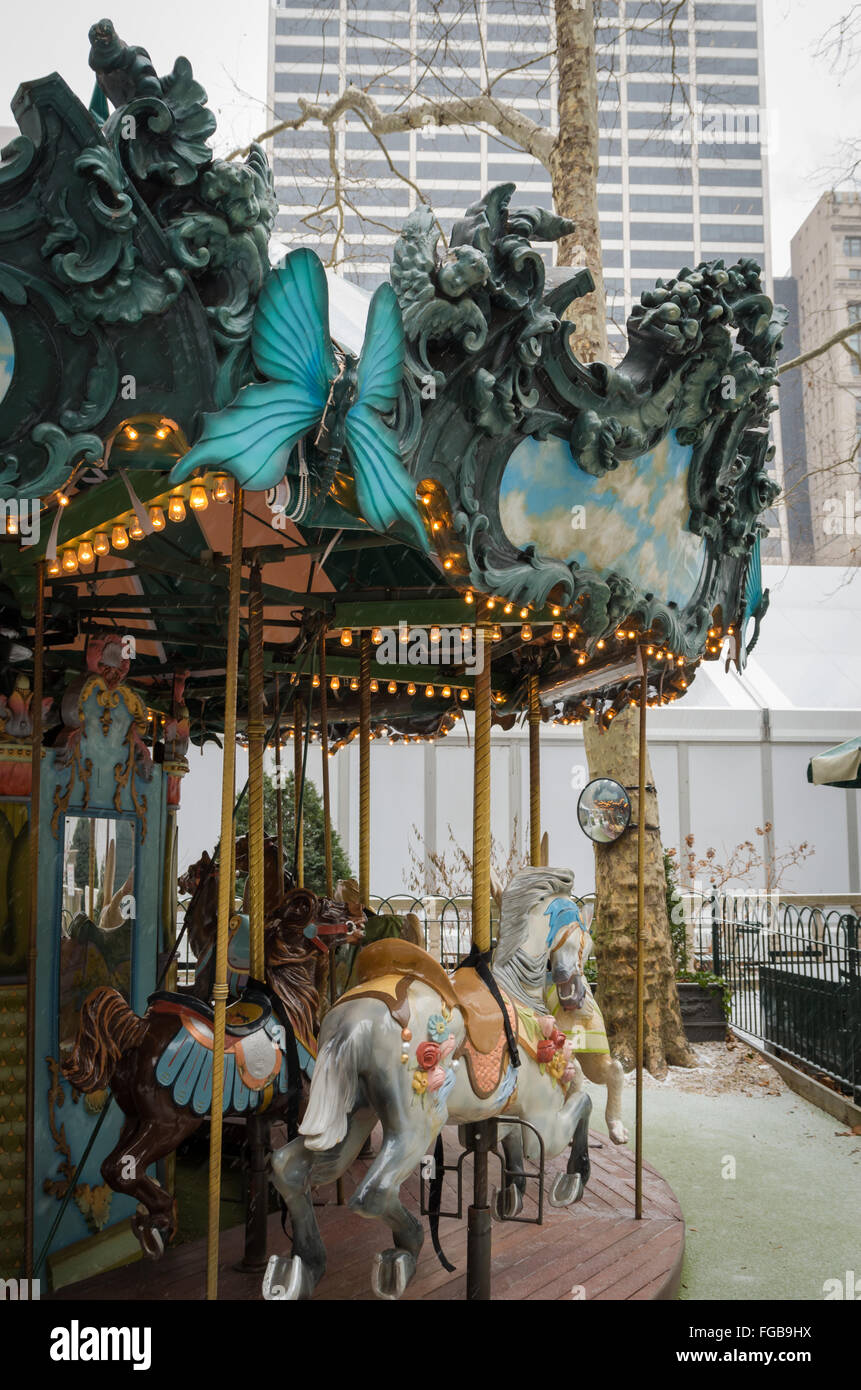 Carousel / Merry-go-round in Bryant Park with elaborate carving and horses, shot in winter as it is snowing. - Stock Image