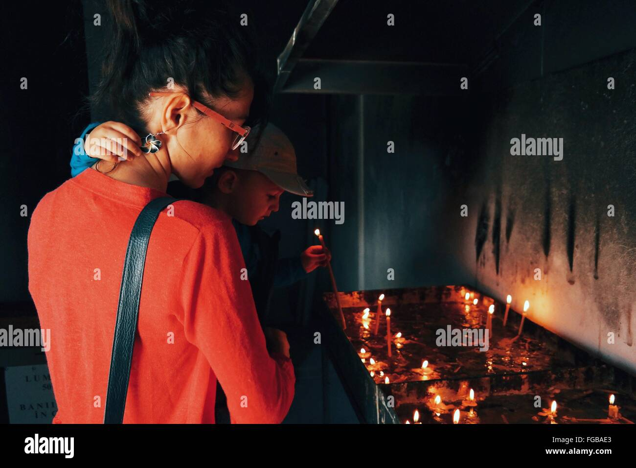 Son Holding Candle With Mother In Church - Stock Image