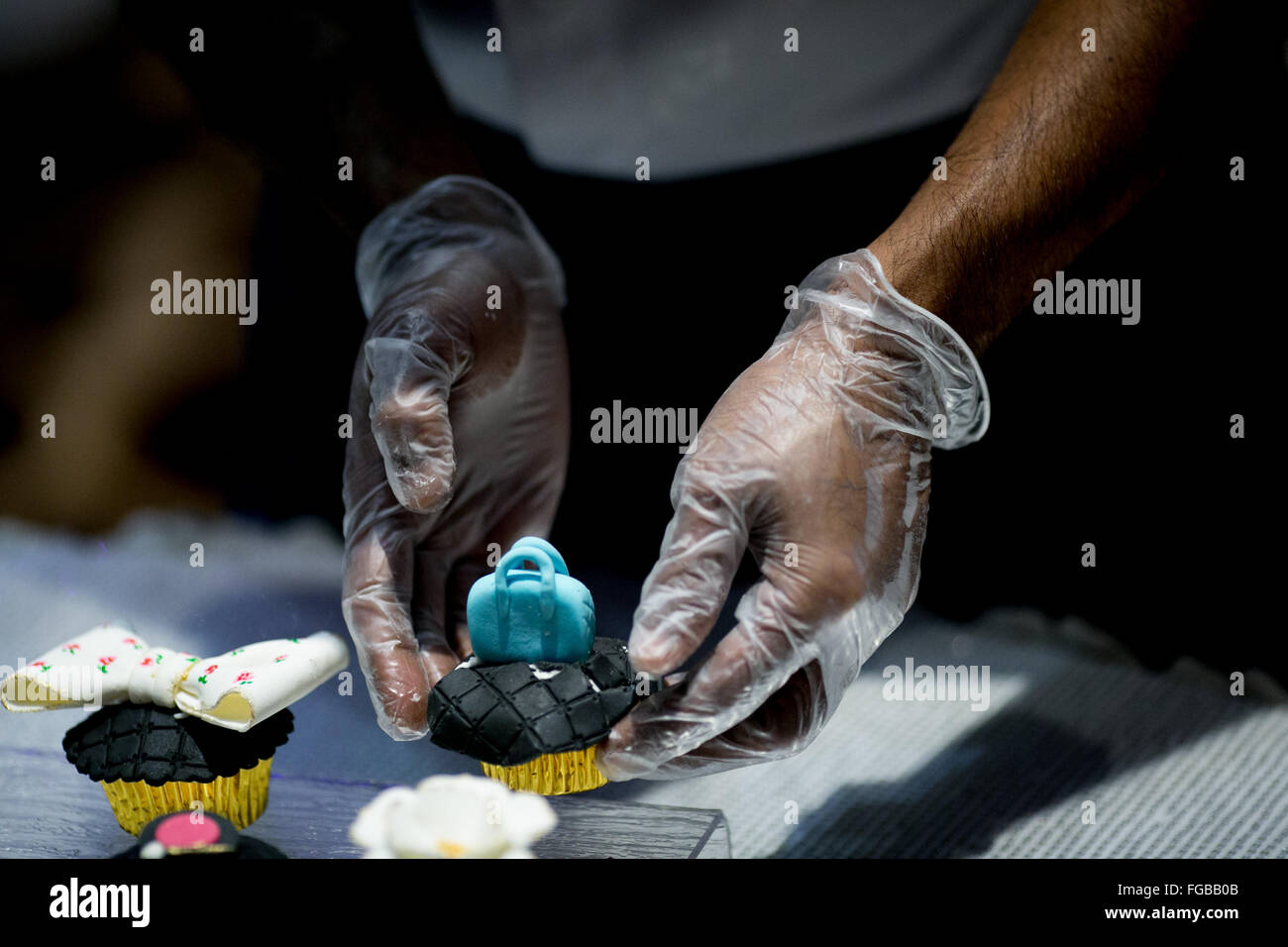 Cropped Image Of Hand Decorating Cupcakes - Stock Image