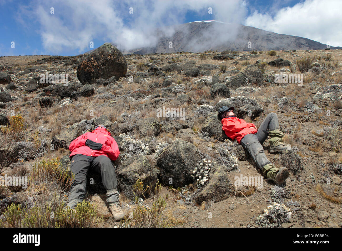 Two hikers are laying exhausted of altitude sickness on the slopes of Mount Kilimanjaro. - Stock Image