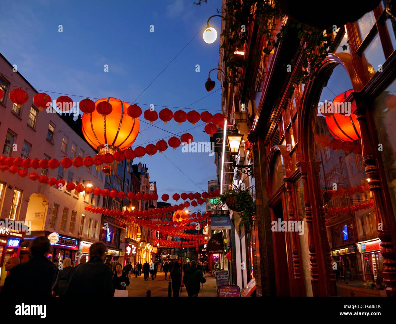 Chinese lanterns lit up on a busy night in Wardour Street Chinatown Soho London UK - Stock Image