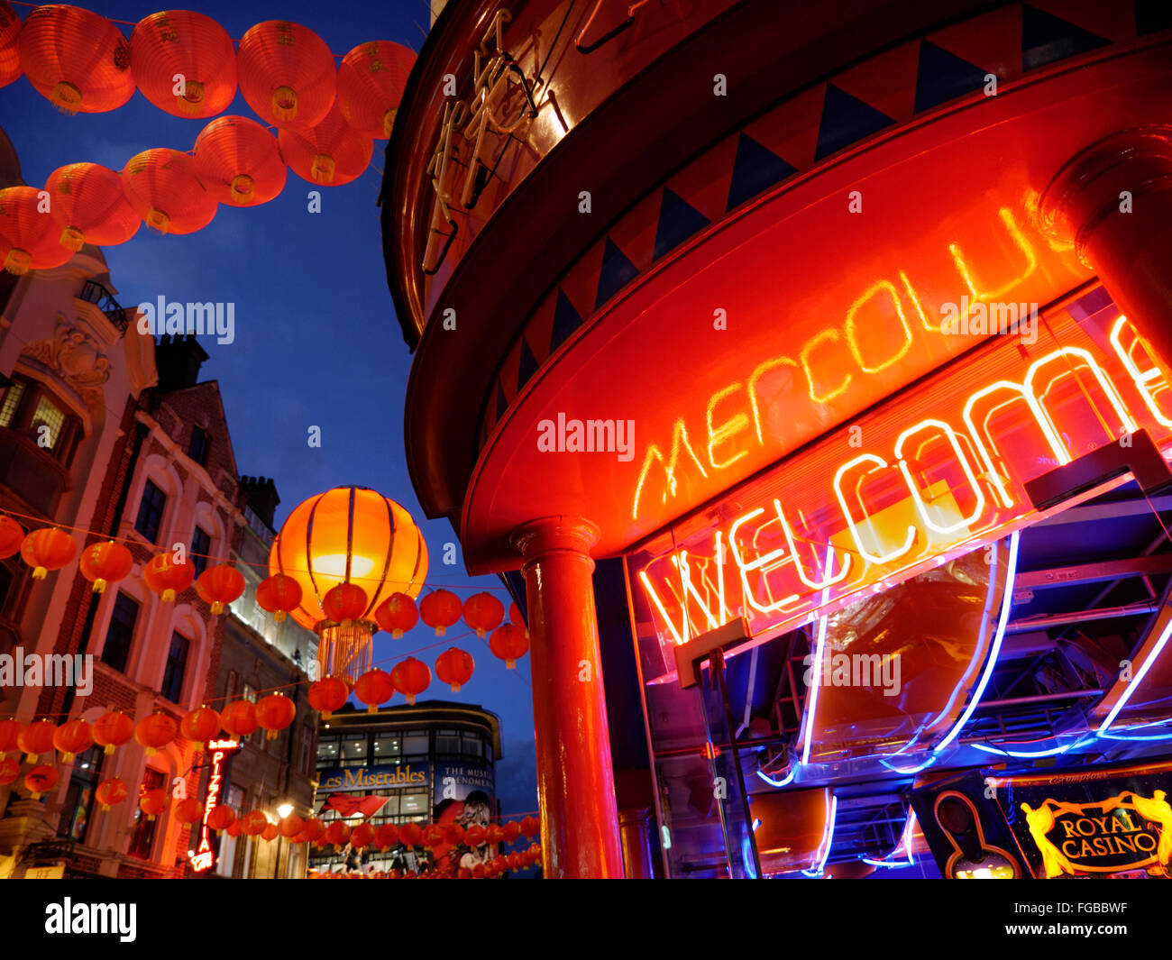 Chinese lanterns lit up on a busy night in Wardour Street with neon 'Welcome' sign Chinatown Soho London - Stock Image