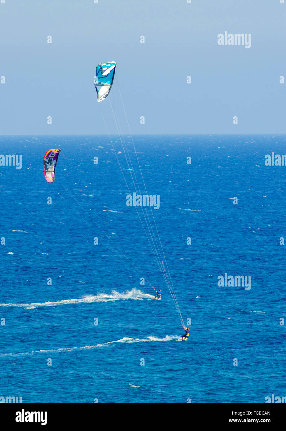 Two men kitesurfing in the crystal bays of Cyprus. A watersport whereby a kite surfer controls a power kite and - Stock Image