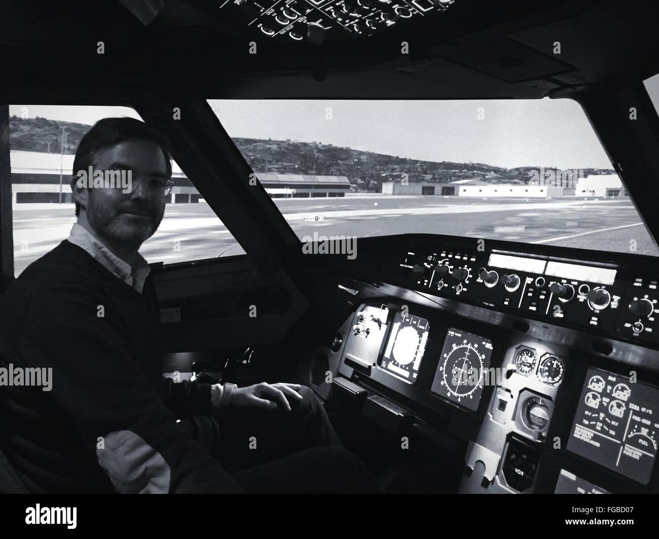 Portrait Of Mature Man Sitting At Cockpit In Airplane - Stock Image