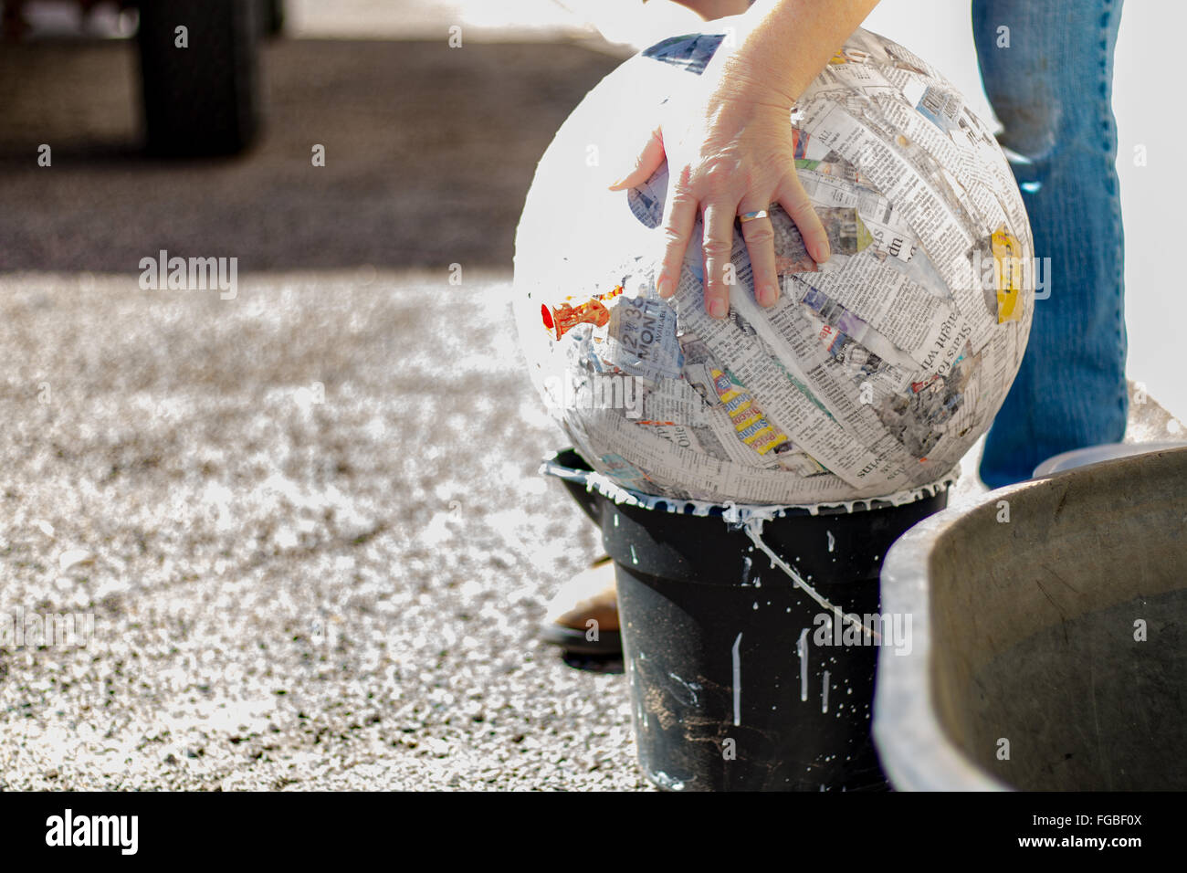 Cropped Image Of Hand Touching Papier Mache Ball On Bucket - Stock Image