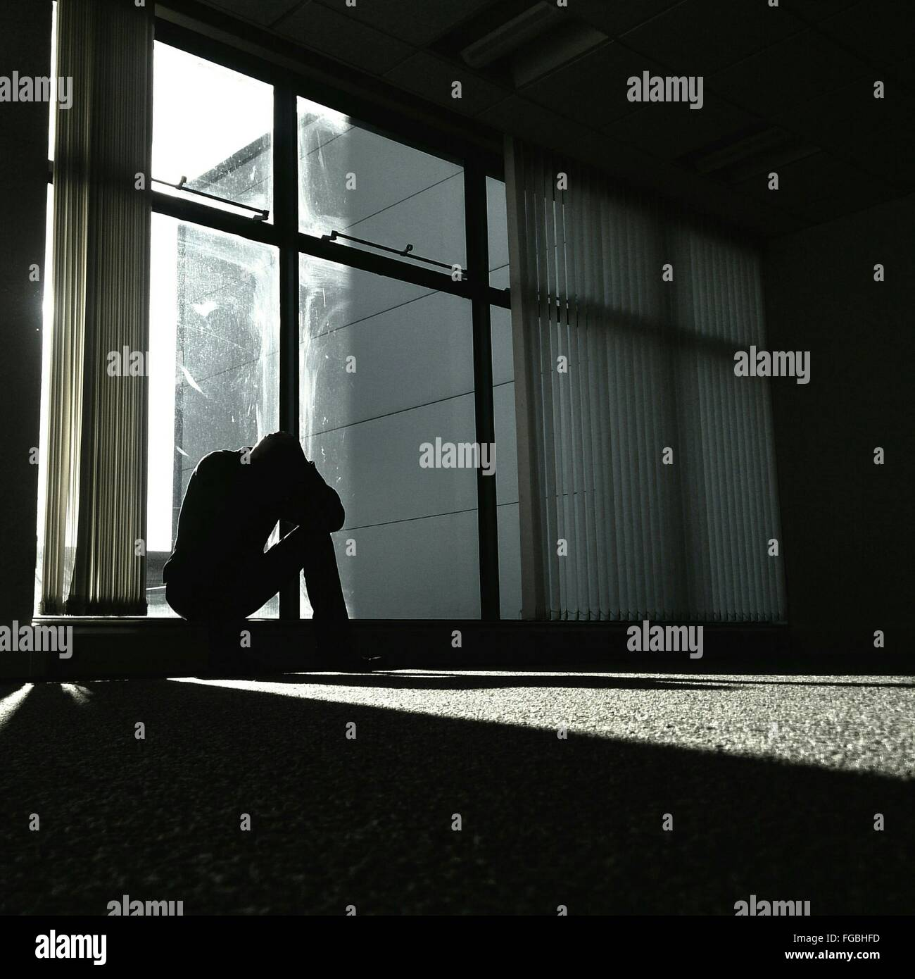 Depressed Man Sitting By Glass Window At Home - Stock Image