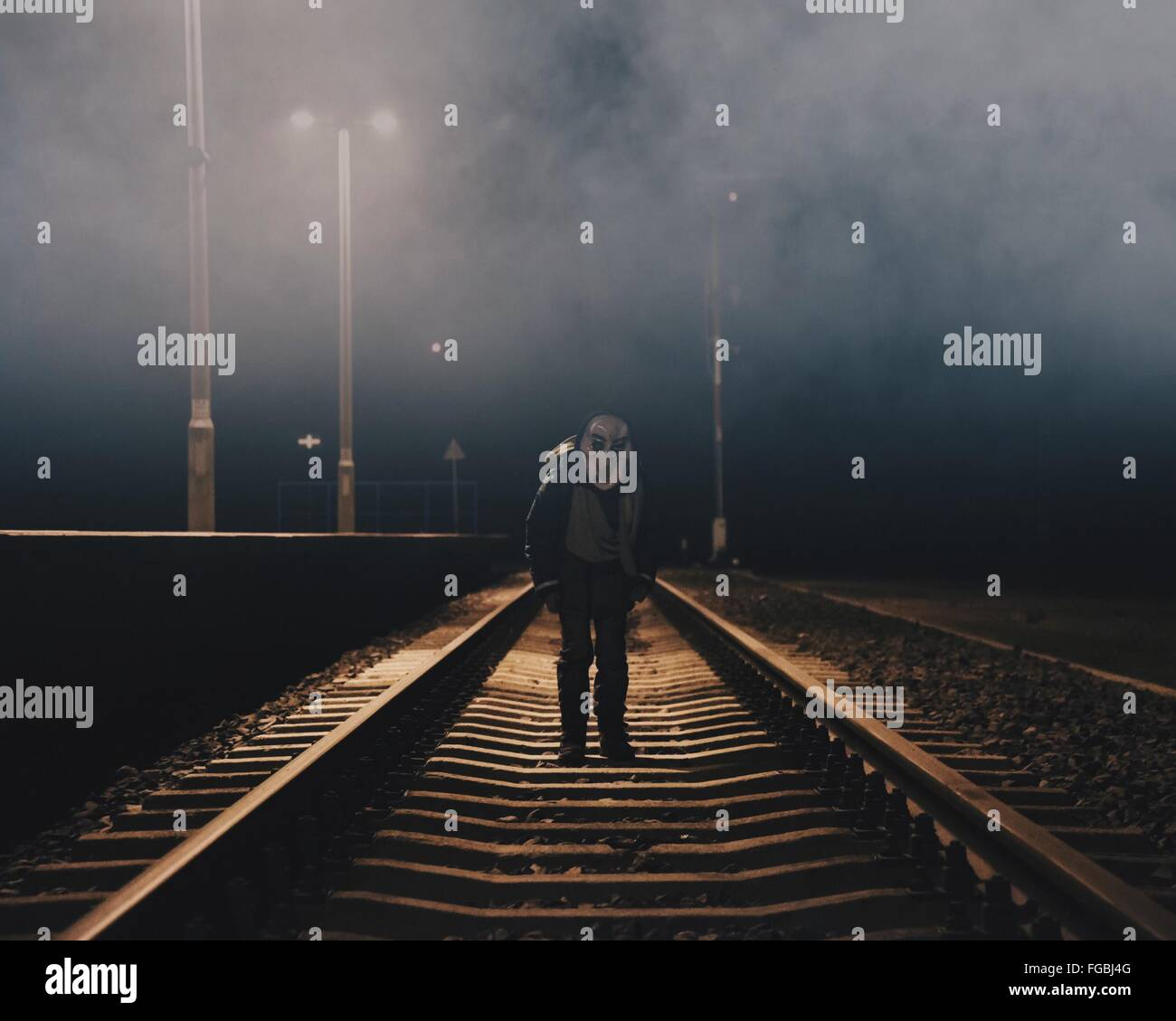 Man Wearing Spooky Mask While Standing On Railroad Track During Halloween - Stock Image