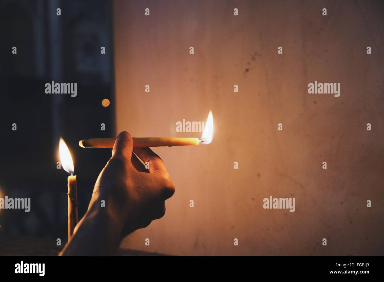 Cropped Hand Holding Lit Candle Against Wall - Stock Image