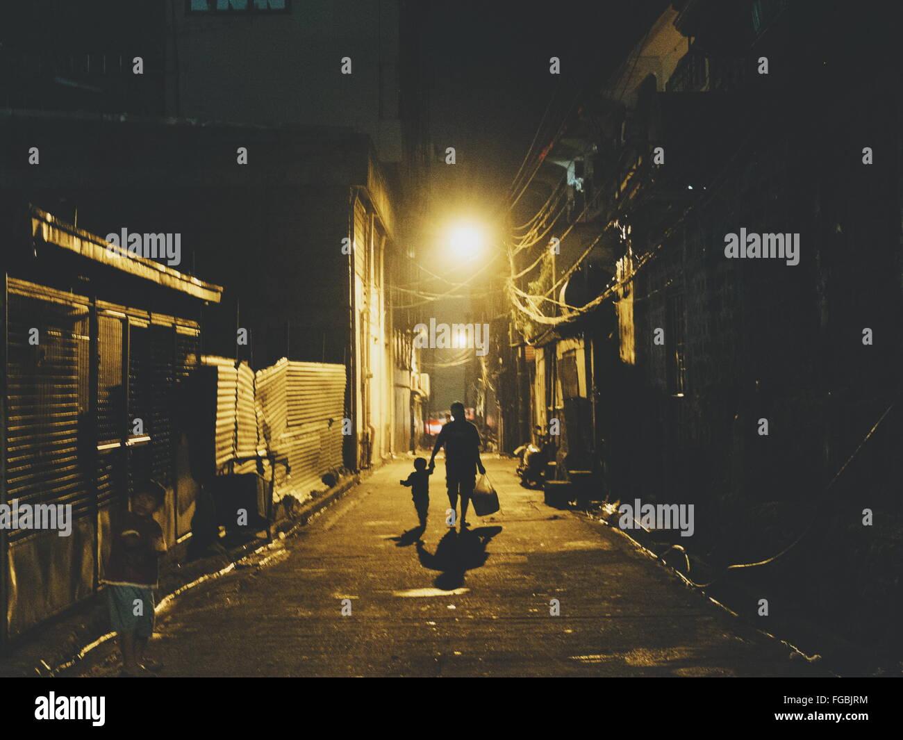 Mother Walking With Child On Illuminated Street At Night - Stock Image