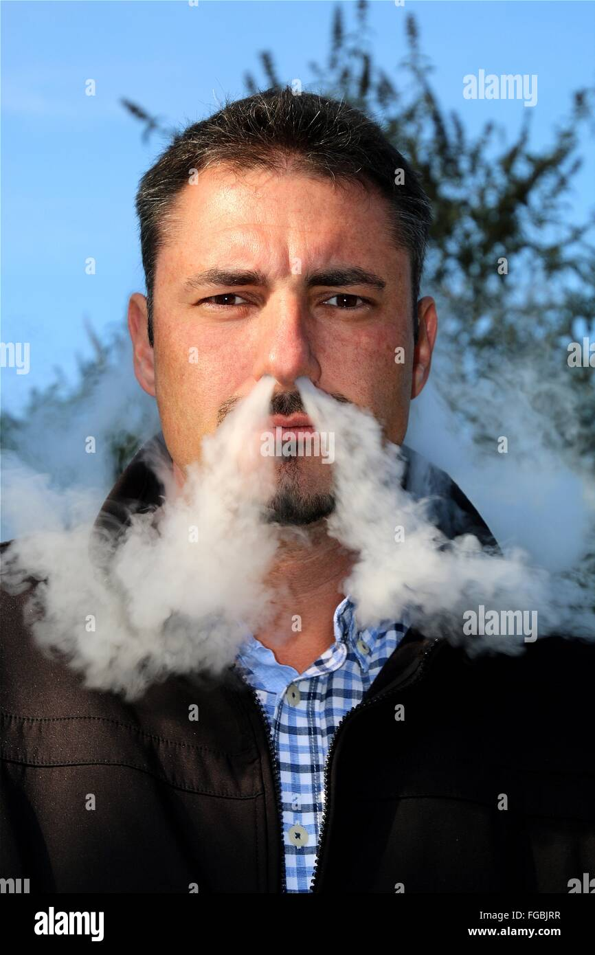 Portrait Of Man Emitting Smoke From Nose Against Sky Stock Photo