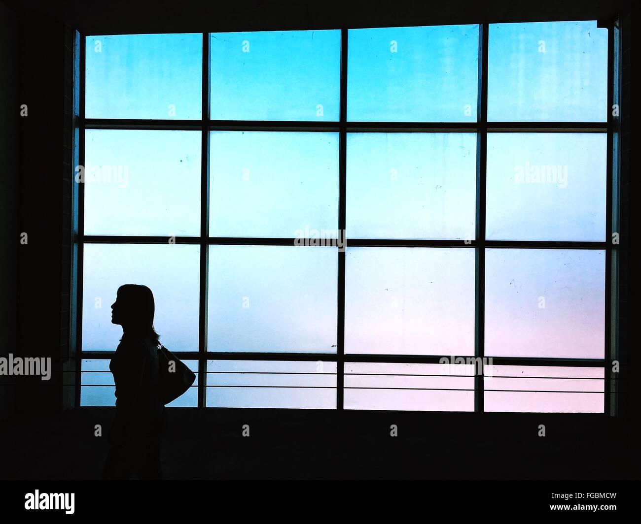 Silhouette Woman Walking In Parking Lot - Stock Image
