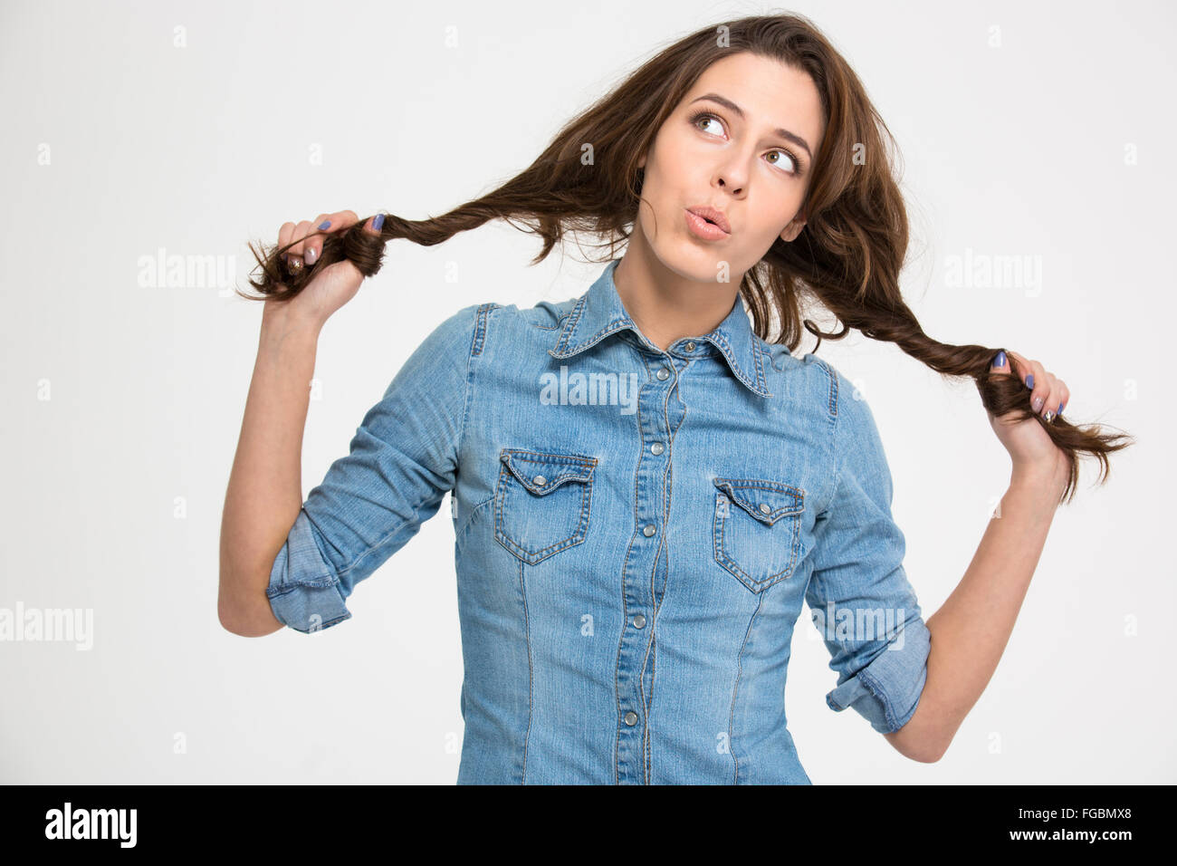 Playful pensive cute young woman grimacing and holding her hair as two braids over white background - Stock Image
