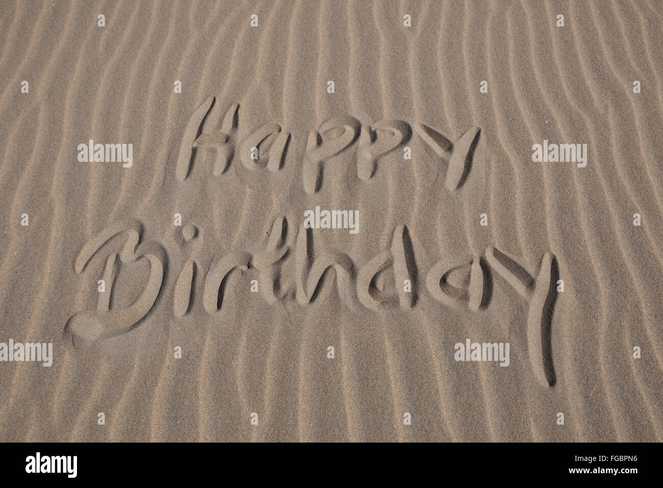 Happy Birthday Text Written On Sandy Beach - Stock Image