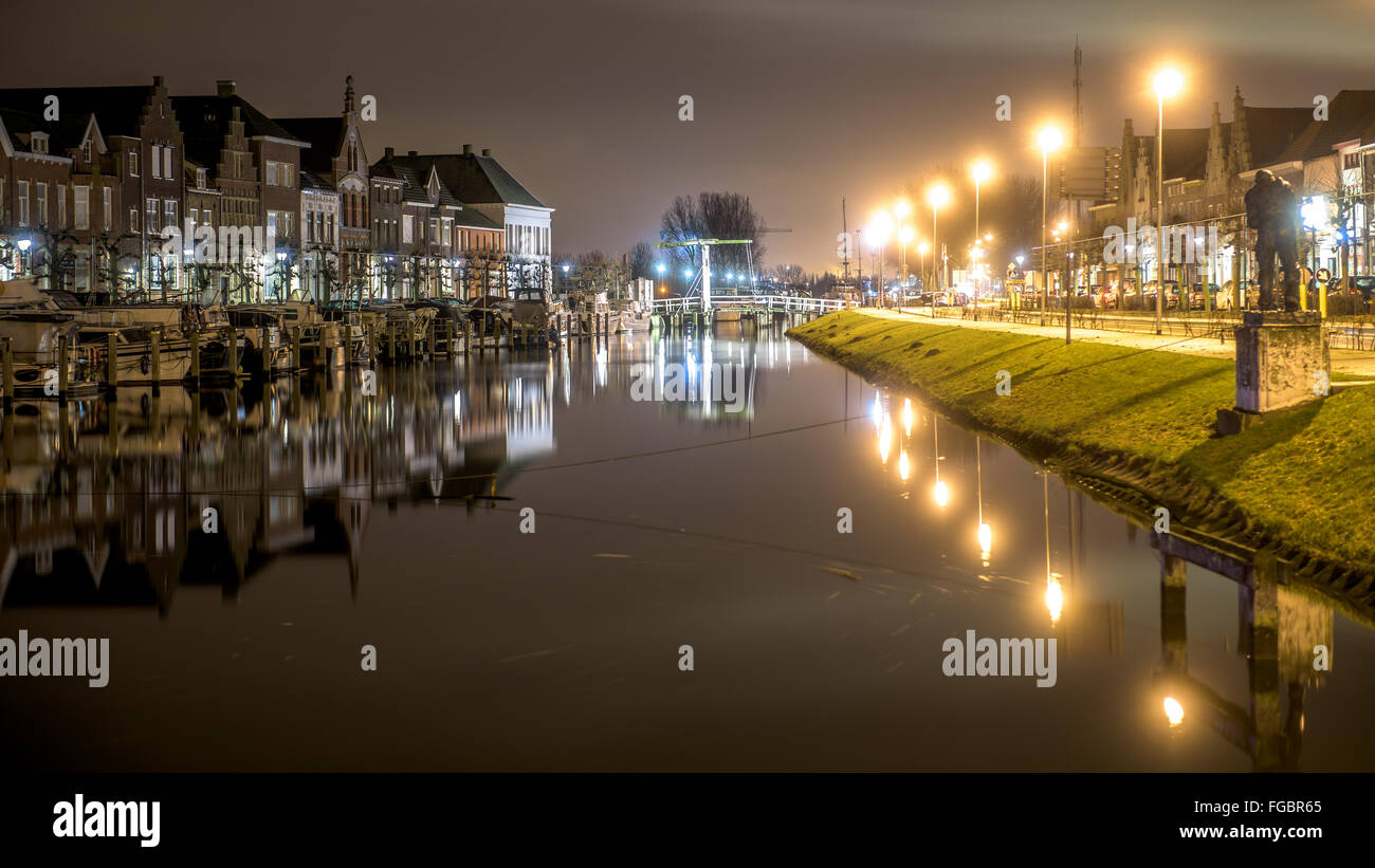 Canal Amidst Industries At Night - Stock Image