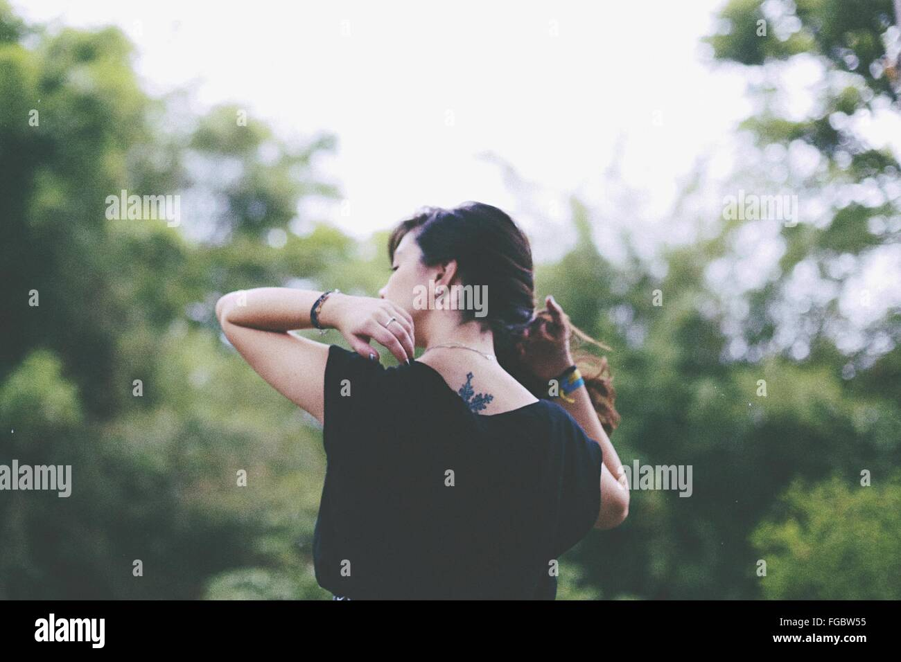 Rear View Of Woman With Hand In Hair Standing On Field - Stock Image