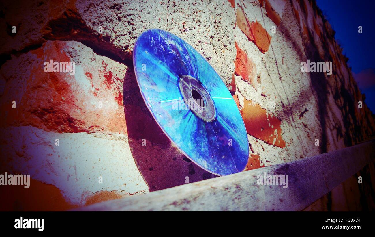 Close-Up Of Abandoned Compact Disc On Wall - Stock Image
