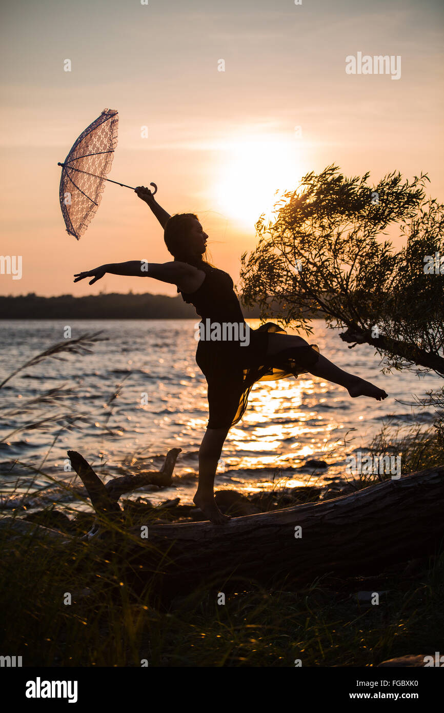 Dancer holding an umbrella walking like a tightrope walker on a driftwood - Stock Image