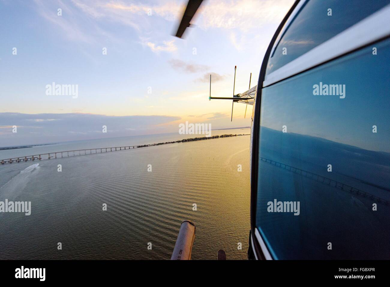 Cropped Image Of Helicopter Flying Over Sea Against Sky - Stock Image
