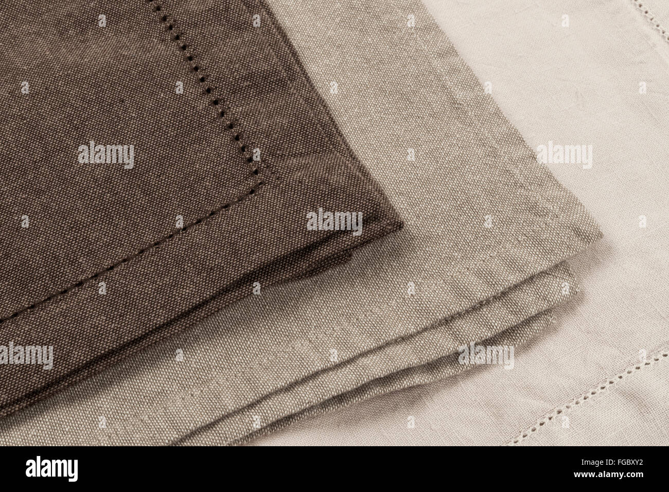 Edges of linen cloth napkins in brown and beige natural colors close up - Stock Image