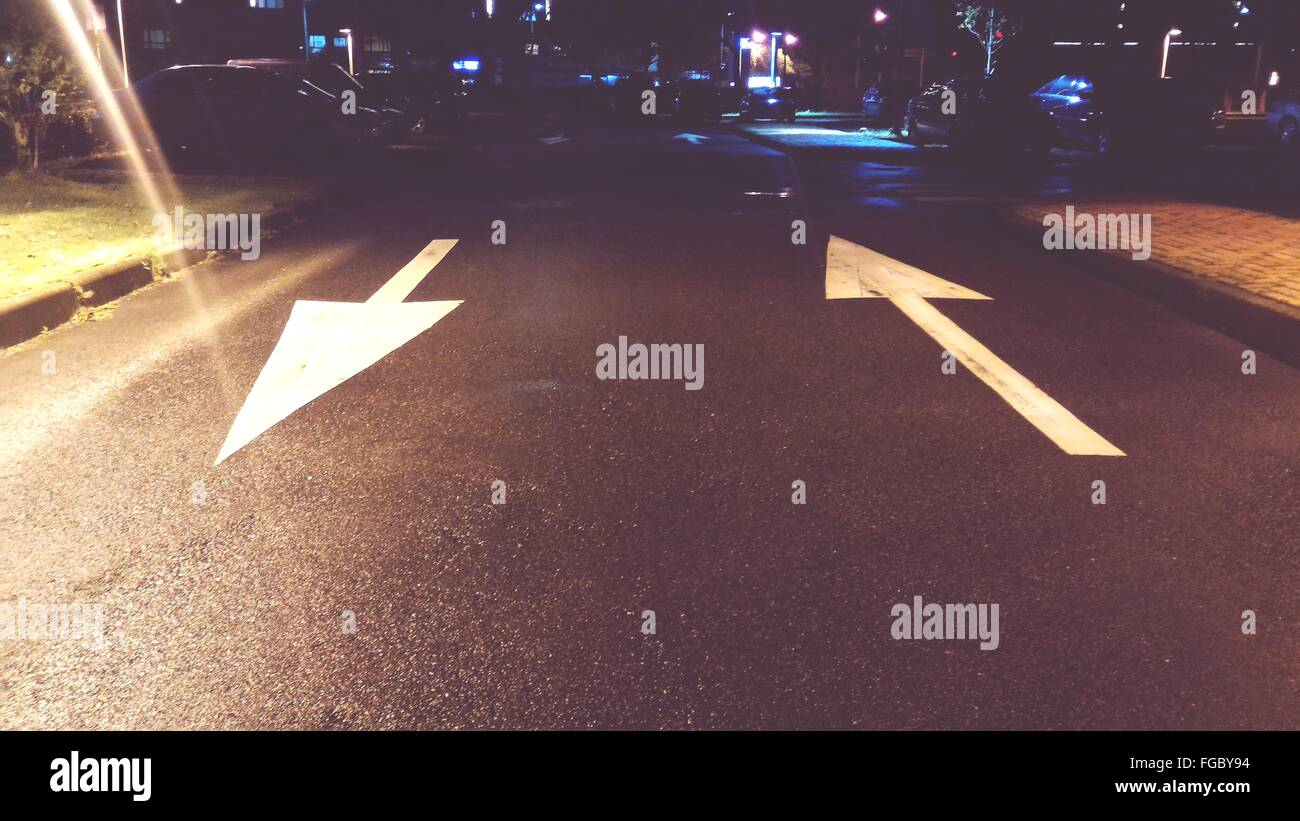 High Angle View Of Arrow Symbols On Road In City At Night Stock