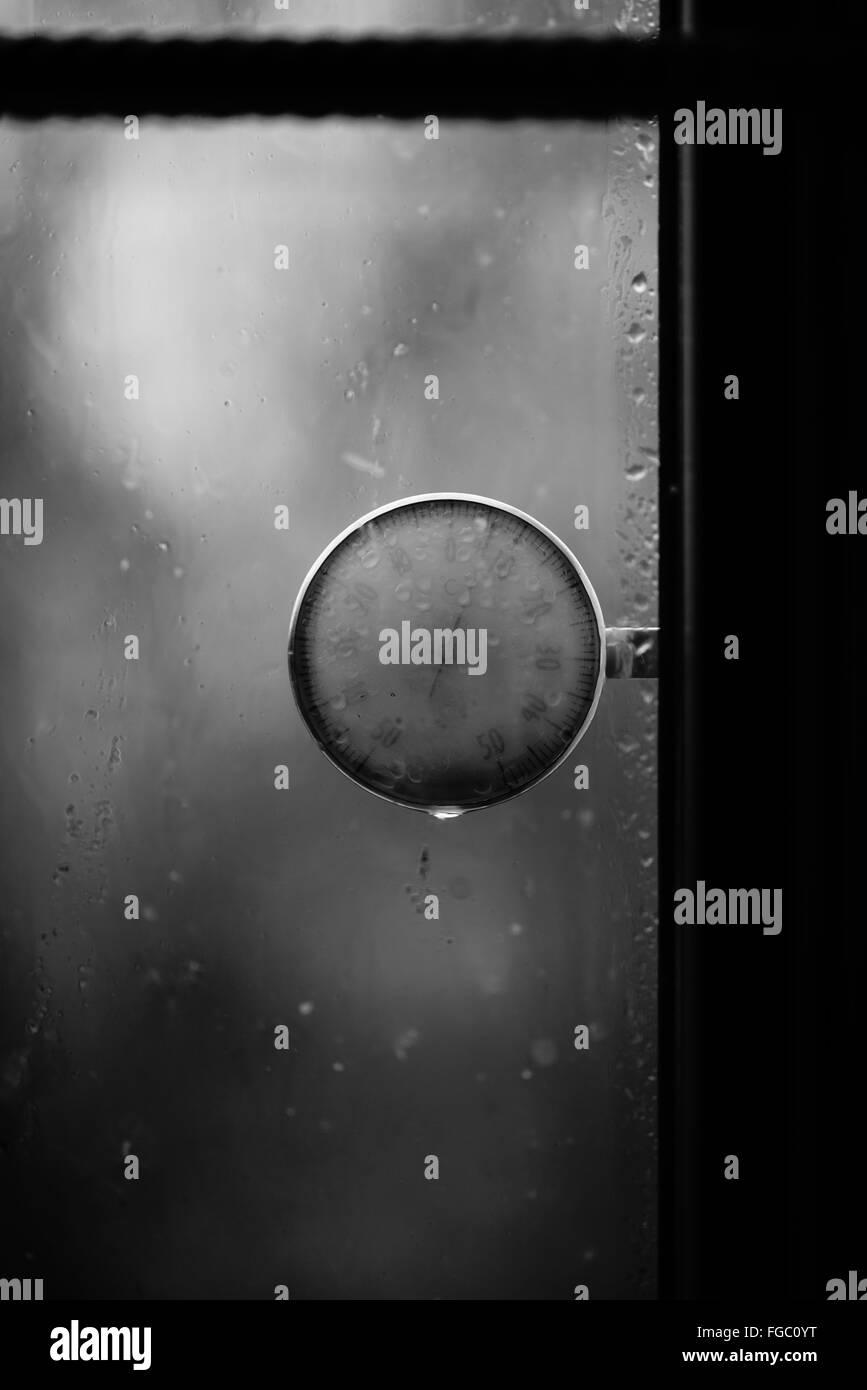 Close-Up Of Meter At Window During Rainy Season - Stock Image