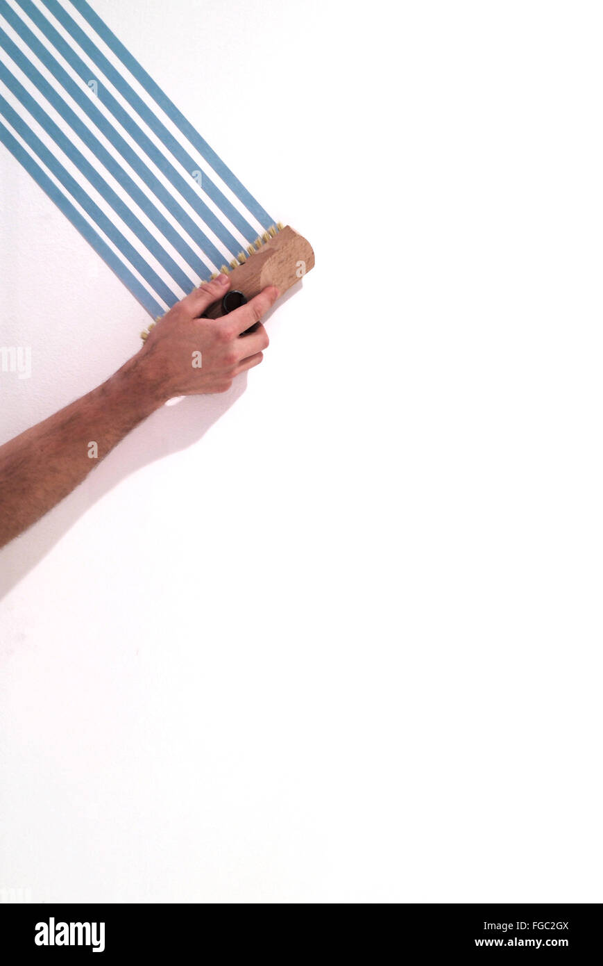 Cropped Image Of Hand Holding Brush While Painting On Wall - Stock Image