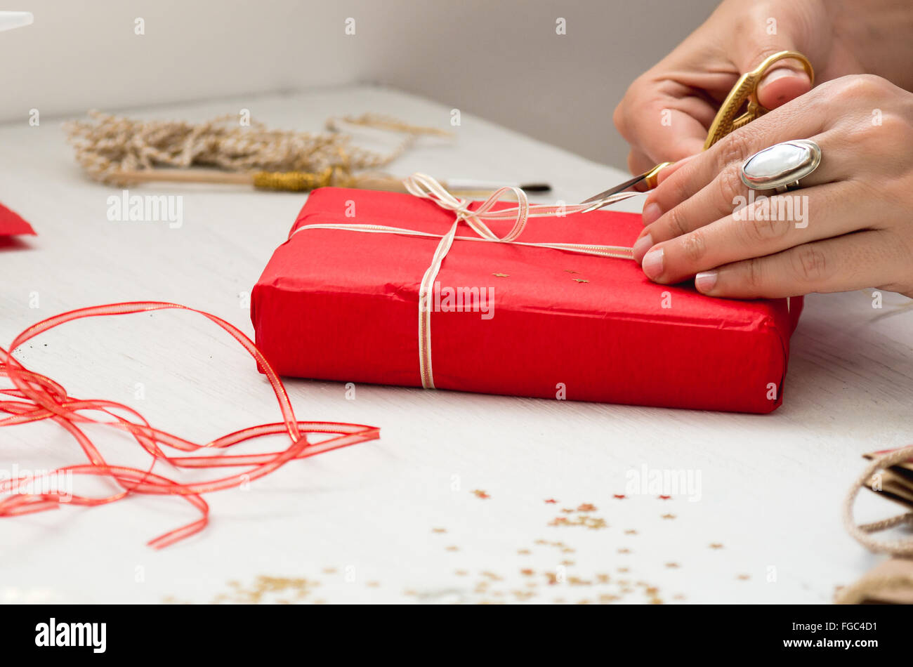 Cropped Image Of Hand Cutting Ribbon On Gift At Table - Stock Image