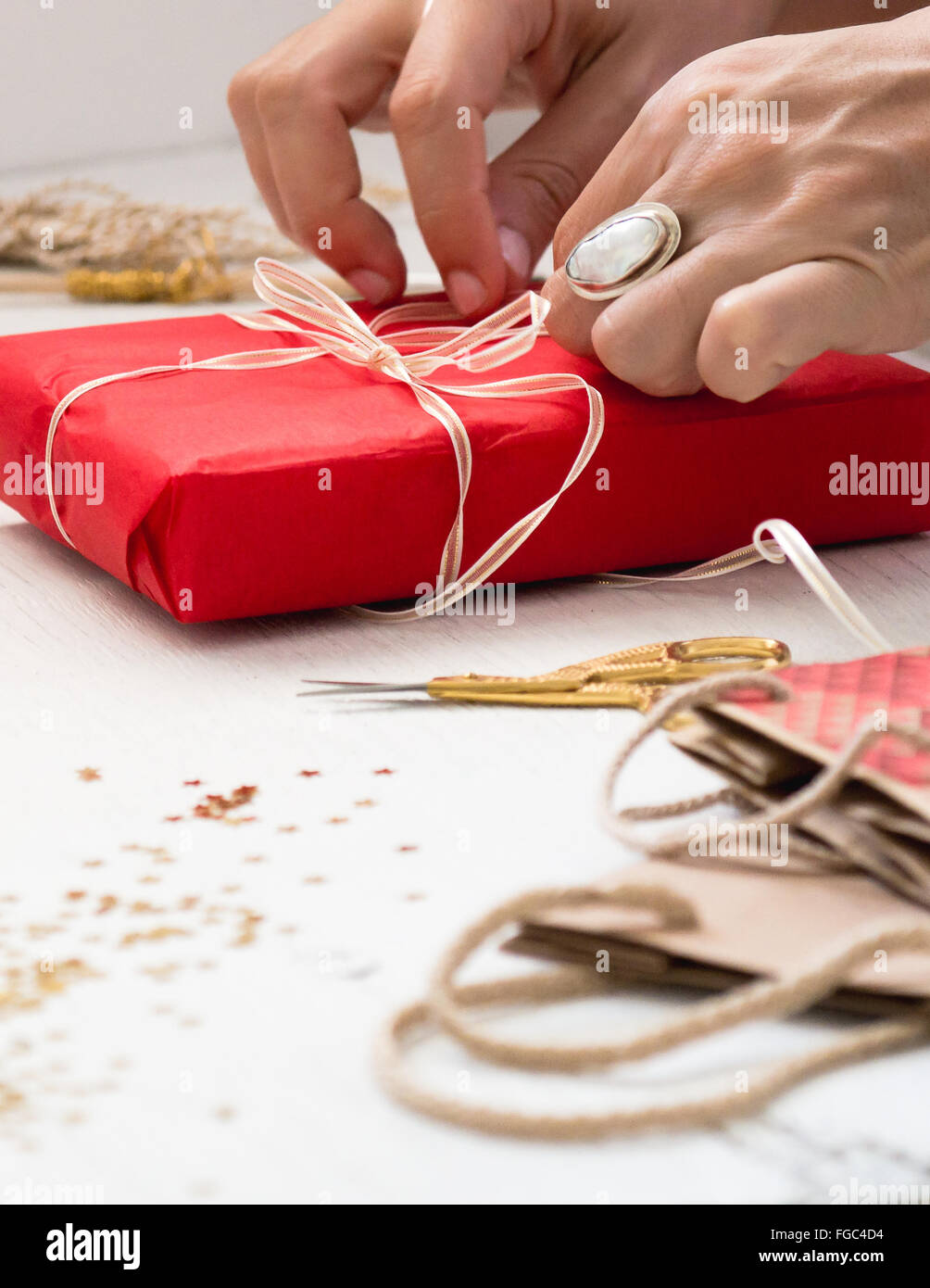Cropped Image Of Hand Tying Ribbon On Gift At Table - Stock Image