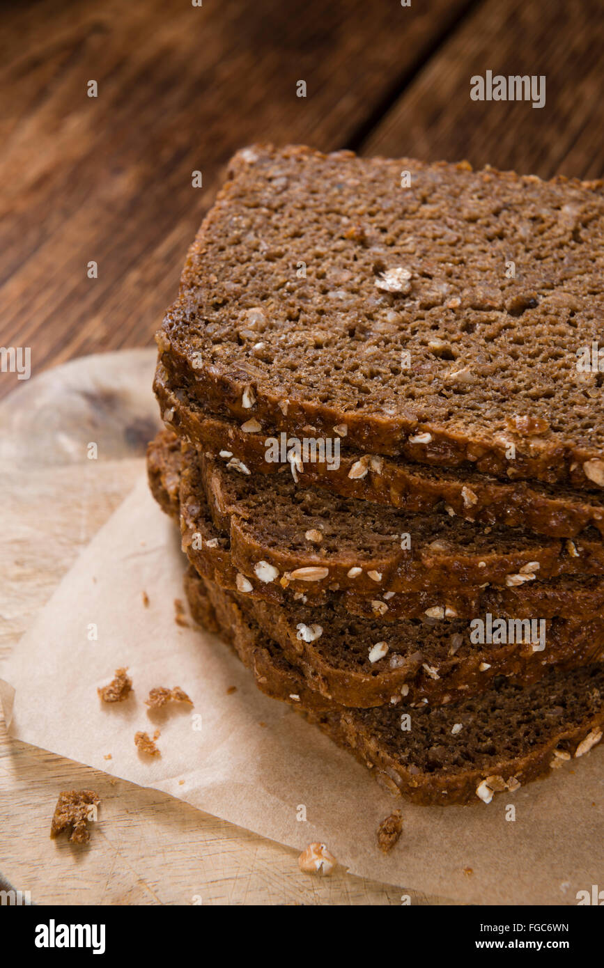 Brown Bread (sliced) on an old wooden table (selective focus) - Stock Image