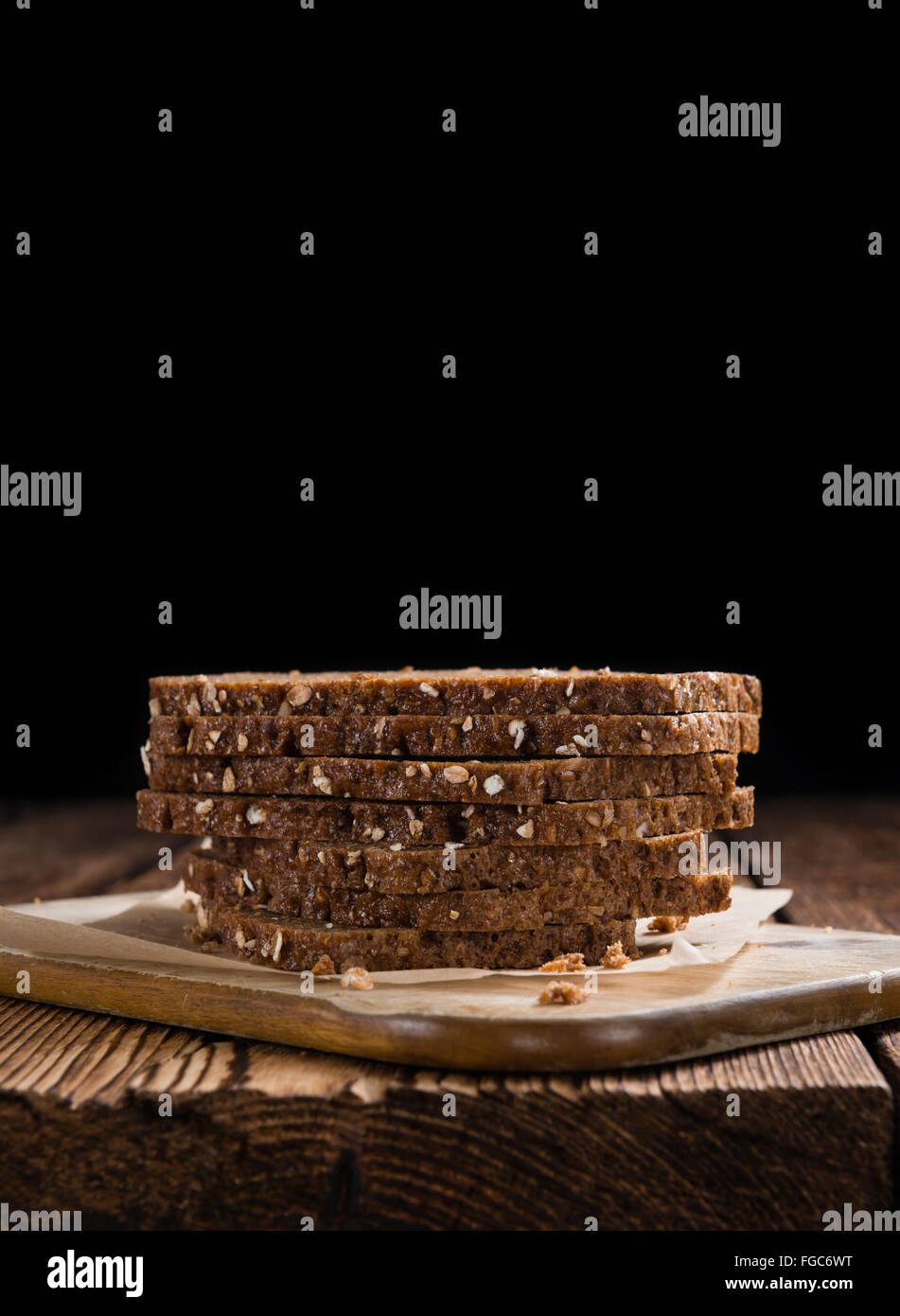 Slices of  Brown Bread (selective focus) on an old wooden table - Stock Image
