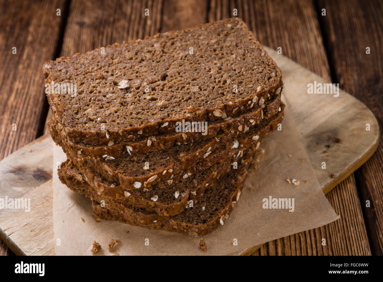 Brown Bread (sliced) on an old wooden table (selective focus) Stock Photo