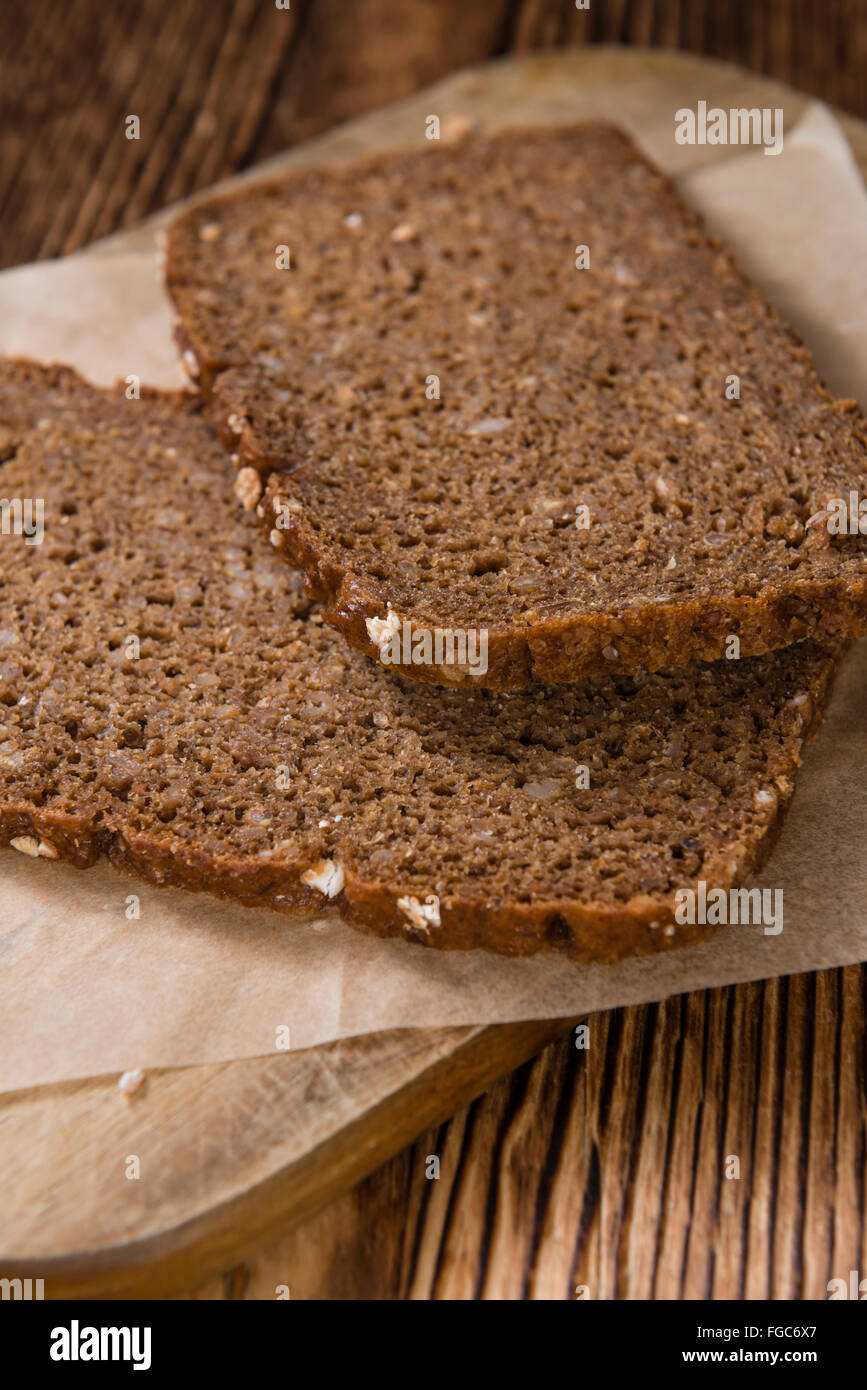 Some slices of brown Bread (selective focus) on wooden background Stock Photo