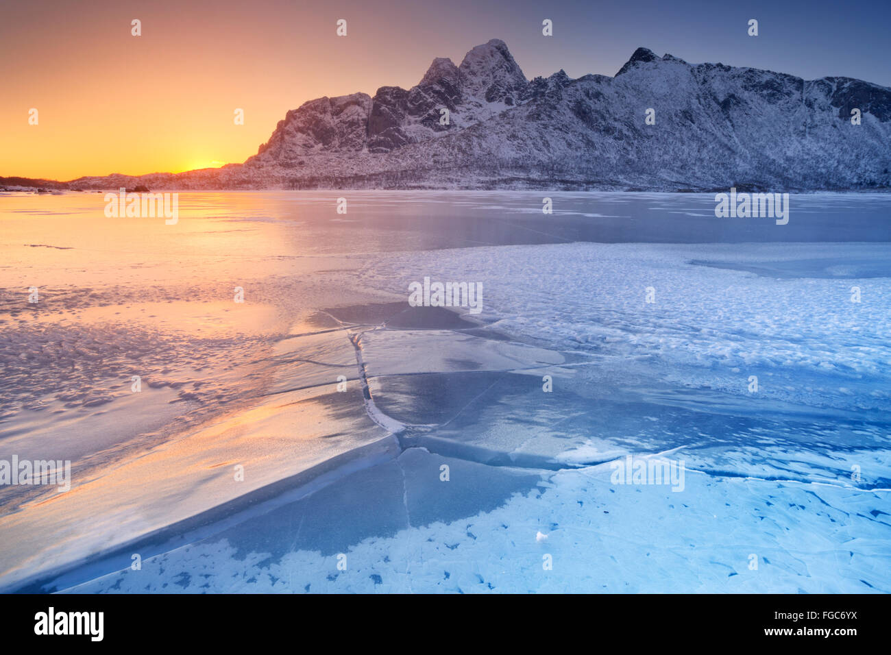 A frozen fjord on the Lofoten in northern Norway with the low midday sun behind the mountains. - Stock Image