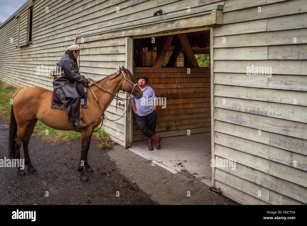 Two gauchos at a stable, one on a horse, Torres del Paine National Park, Patagonia, Chile, South America - Stock Image