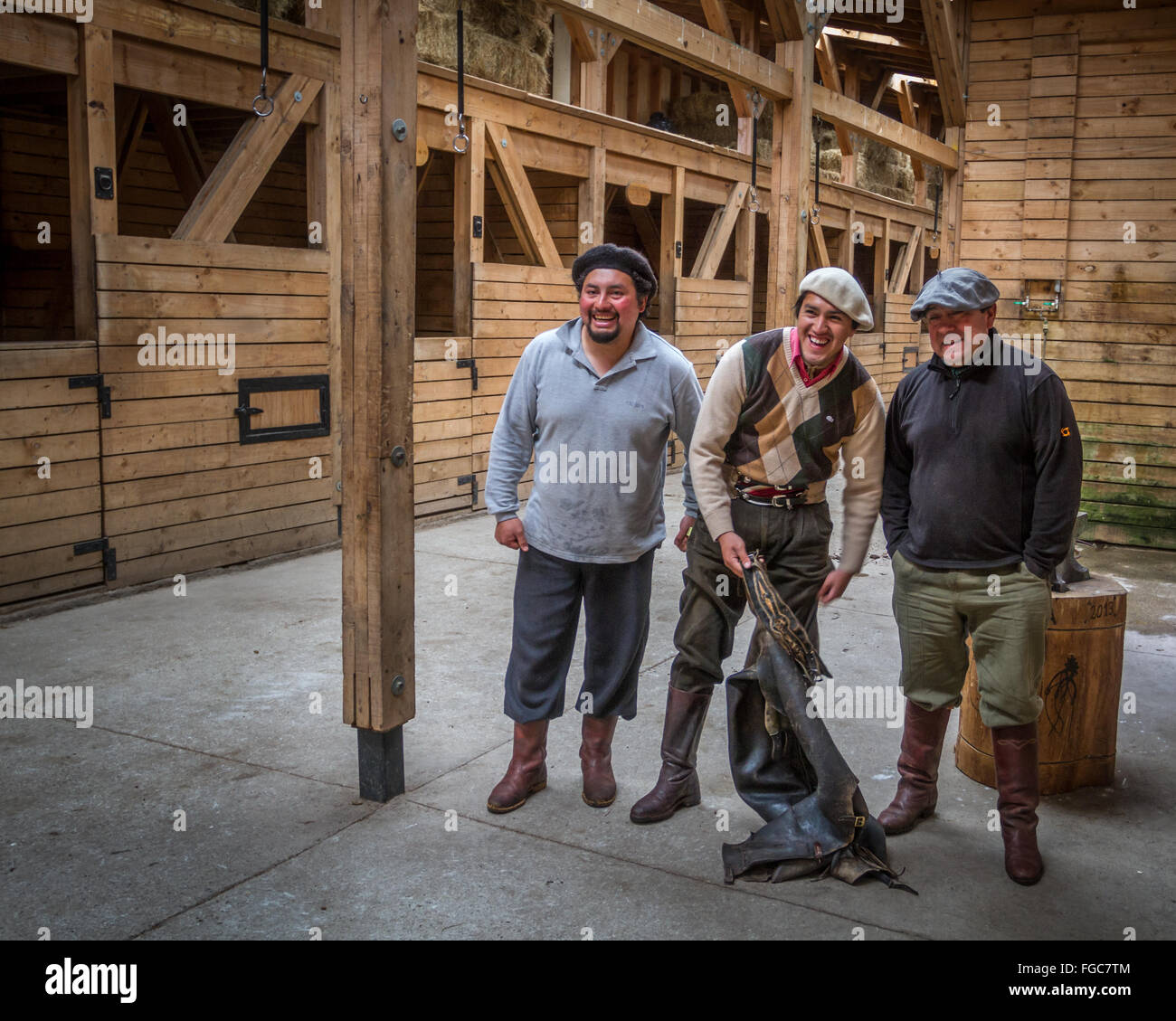 Three gauchos wearing traditional hats inside a stables smiling horse riding gear, Patagonia, Chile - Stock Image