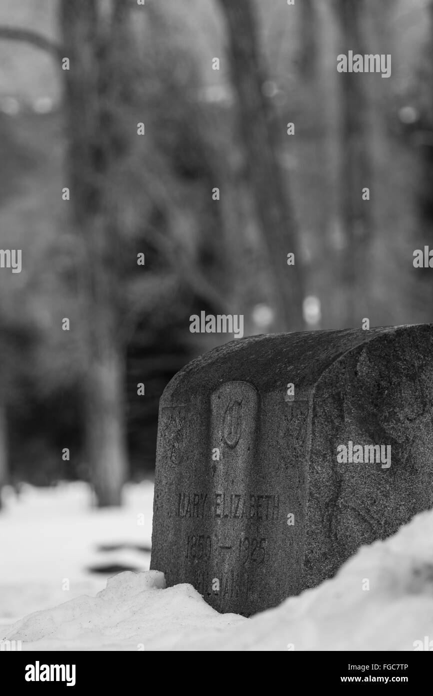Head Stone in the Snow - Stock Image