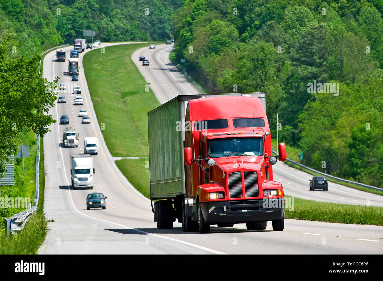 Red Semi Truck Climbing Hill On Interstate Highway - Stock Image