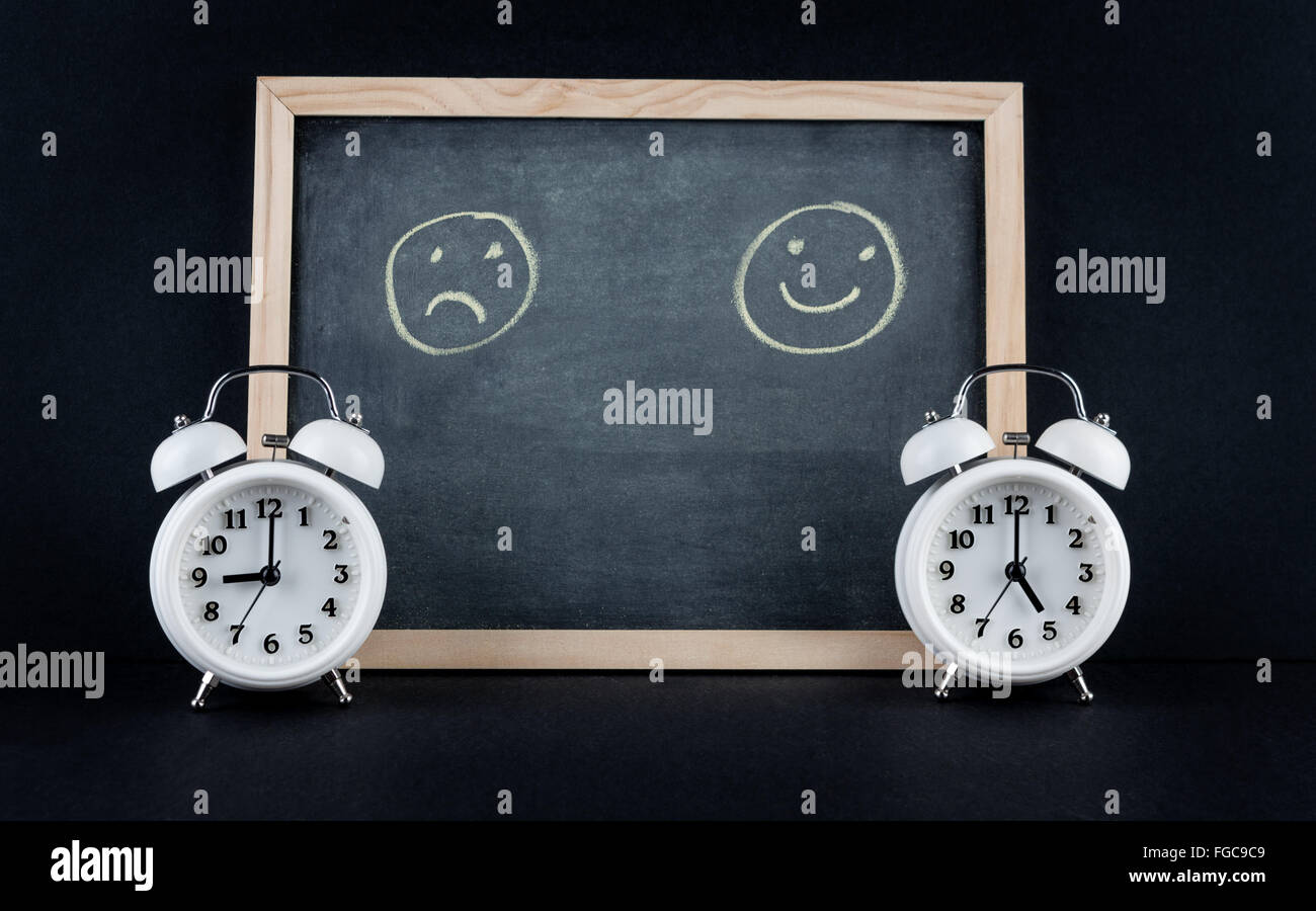Two vintage alarm clocks showing 9 and 5 o'clock with happy and sad smileys on chalkboard on black background. Nine to five corp Stock Photo