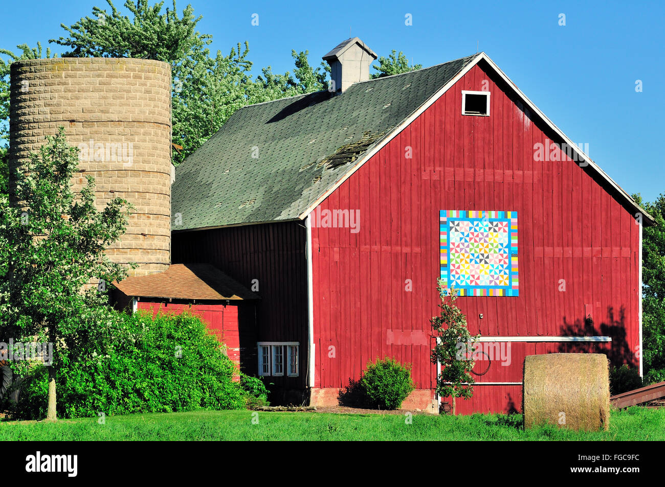 A highly colorful veteran barn basks in the early evening sun on a summer afternoon in northeastern Illinois. - Stock Image
