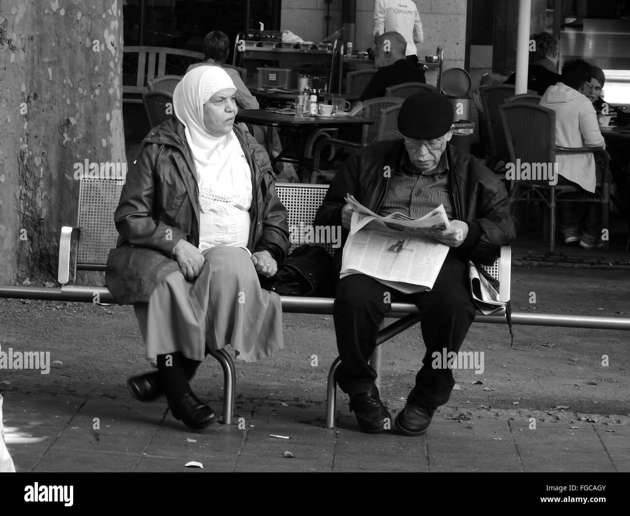 people sitting on a bench, man reading newspaper, Bonn, Bottlerplatz, Germany - Stock Image