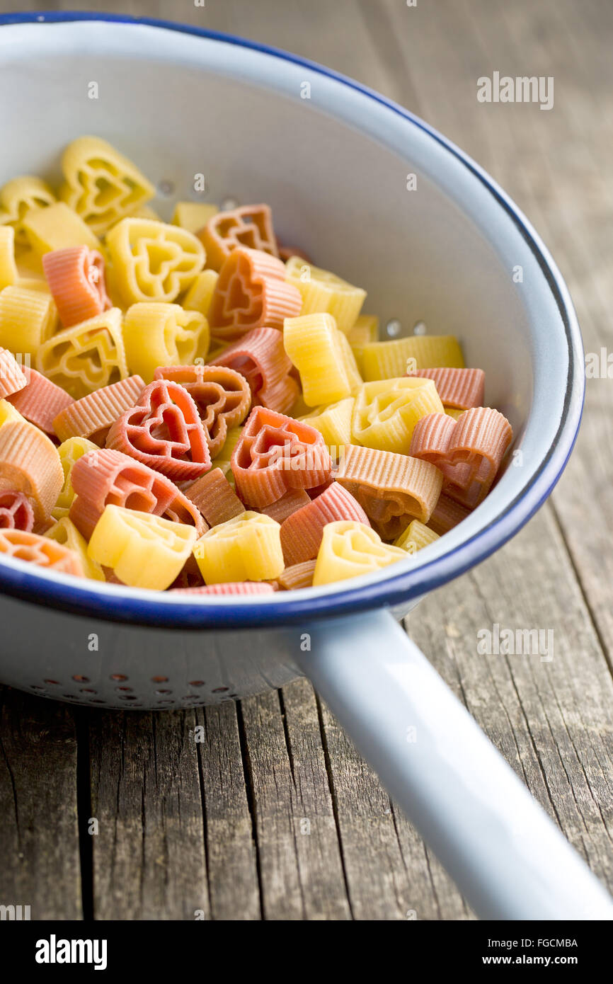 heart shaped pasta in colander - Stock Image