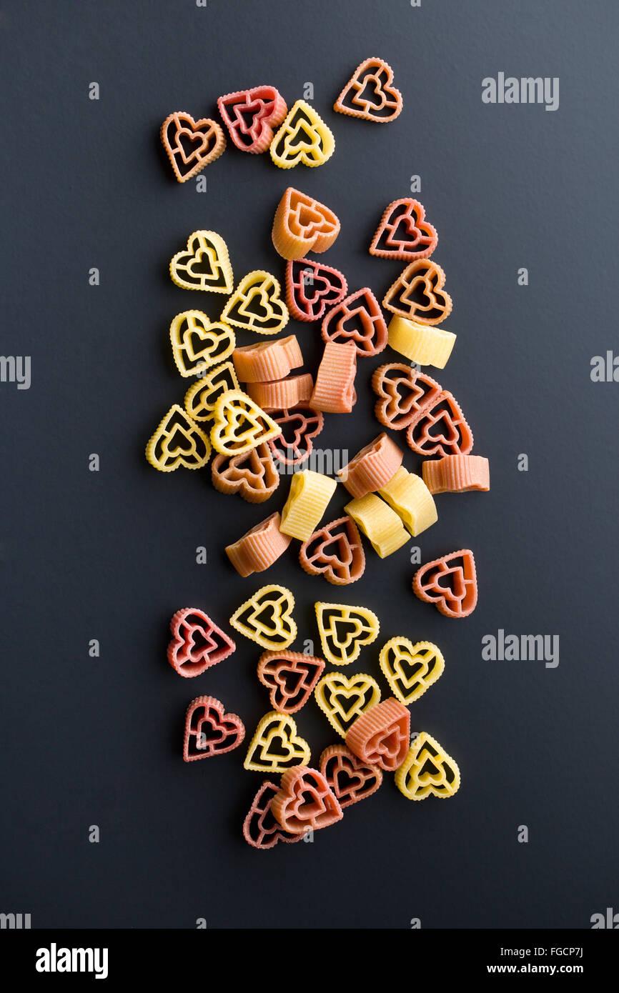 heart shaped pasta on black background - Stock Image